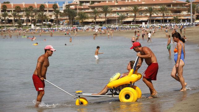 deux personnes accompagne une autre dans une chaise amphibie pour accéder à la mer